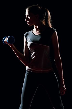 Beautiful sport woman doing power fitness exercise at sport gym. Dumbbell on black photo
