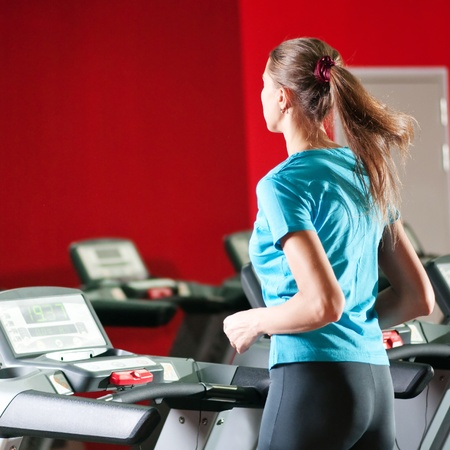 Young woman at the gym exercising. Run on on a machine. Stock Photo - 10055675