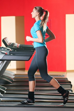 Young woman at the gym exercising. Run on on a machine.  Stock Photo