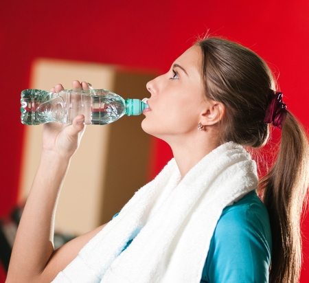 Portrait of a woman at the gym drinking water  Stock Photo