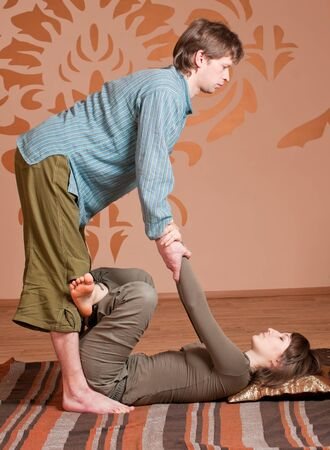 Two young man and woman couple doing yoga. Massage photo