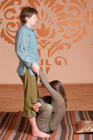 Two young man and woman couple doing yoga. Massage Stock Photo - 9839327