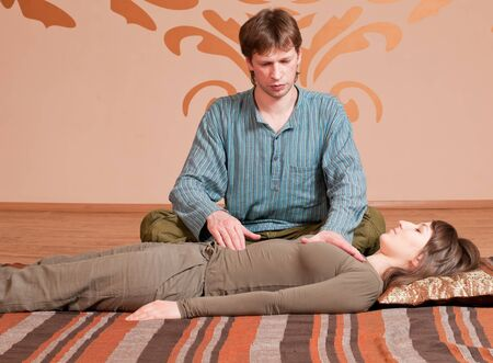 Two young man and woman couple doing yoga. Massage Stock Photo - 9839306