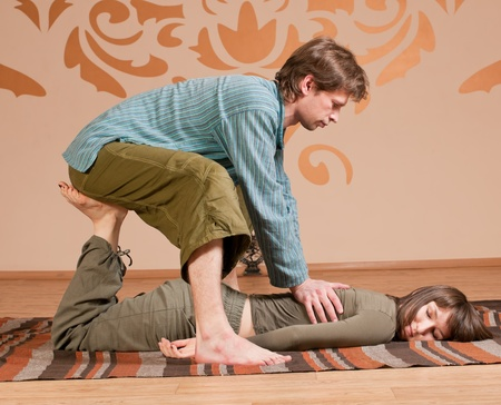 Two young man and woman couple doing yoga. Massage Stock Photo - 9839218