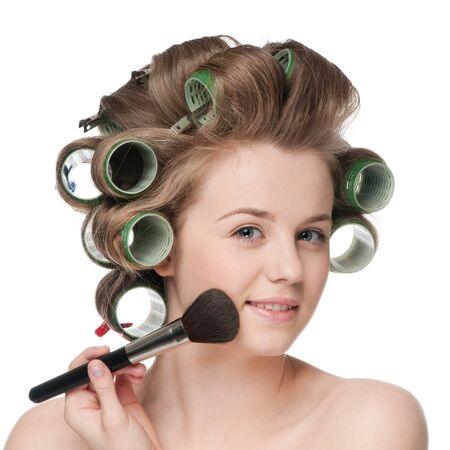 curlers: Beautiful young adult woman in hair roller applying cosmetic powder brush - close-up portrait