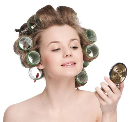 Beautiful young adult woman in hair roller looking in mirror - close-up portrait photo