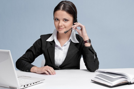 Busy business woman in office place talking by wireless headset over white table, laptop and diary. Sure photo