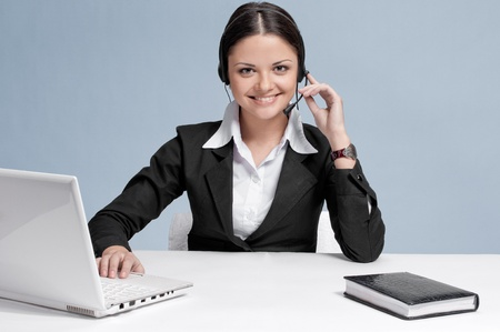 Busy business woman in office place talking by wireless headset over white table, laptop and diary. Smile photo