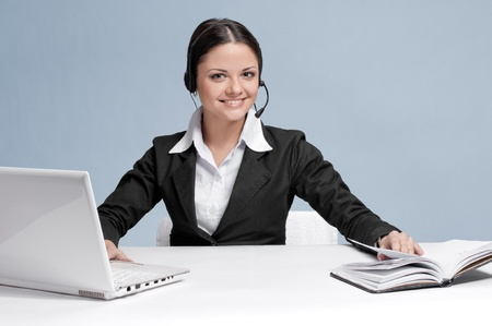 Busy business woman in office place communicate by wireless headset over white table, laptop and diary photo