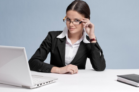 Casual business woman in office working with white table, laptop and phone. Sure photo