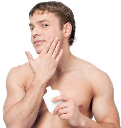 Man putting on cream lotion for face photo