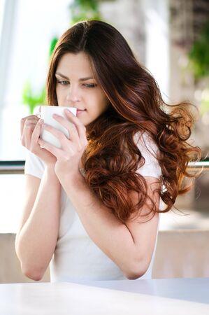 mujeres sentadas: Una mujer atractiva joven sentado en un caf� con un caf�