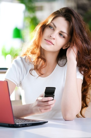 A young attractive business woman sitting in a cafe with a laptop and cell phone photo
