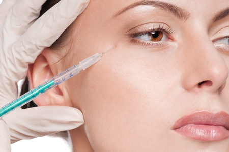 plastic glove: Cosmetic botox injection in the female face. Eye zone. Isolated Stock Photo