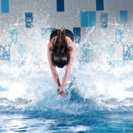 Portrait of a young woman jumping in swimming pool photo