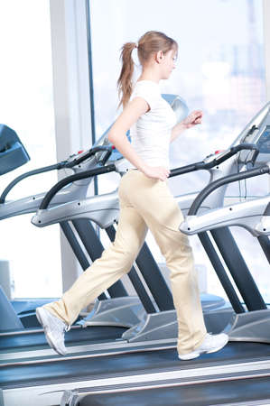 Young woman at the gym exercising. Run on on a machine. Stock Photo - 9999889