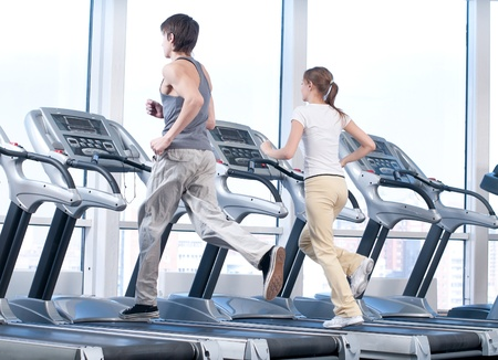 Young woman and man at the gym exercising. Run on on a machine. Stock Photo - 9999926