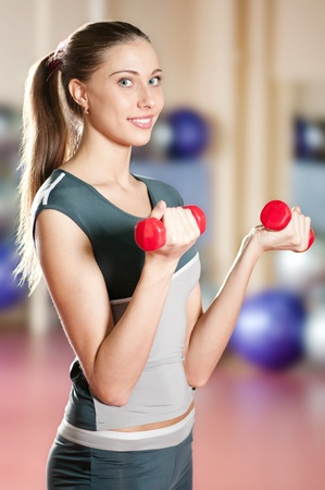 Beautiful sport woman doing power fitness exercise at sport gym. Dumbbell Stock Photo - 10000011