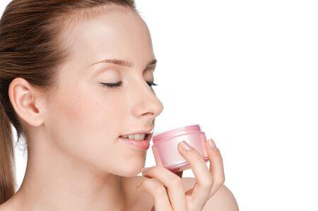 Young beautiful girl smell cream jar photo