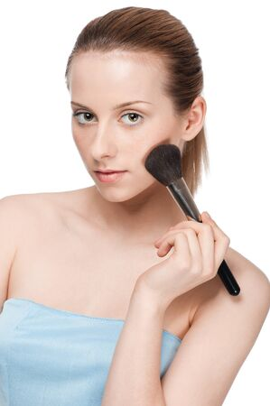 Beautiful young adult woman applying cosmetic powder brush - close-up portrait photo
