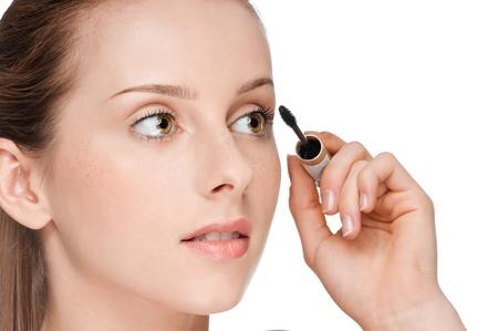 Beautiful woman applying mascara on her eyelashes - isolated on white photo