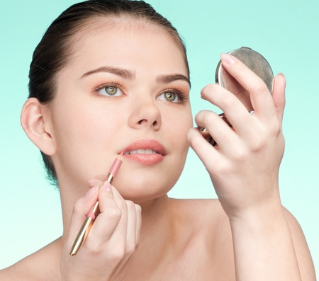 Beautiful young adult woman applying cosmetic lipstick pencil - close-up portrait Stock Photo - 9999957