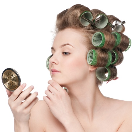 hair roller: Beautiful young adult woman in hair roller looking in mirror - close-up portrait