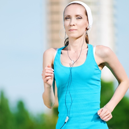 Beautiful woman with headphones running in green park on sunny summer day Stock Photo - 10203287