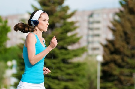 jogging in park: Beautiful woman with headphones running in green park on sunny summer day