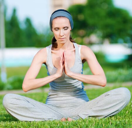 Beautiful woman doing stretching exercise on green grass at park. Yoga Stock Photo - 10203881