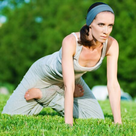 Beautiful woman doing stretching exercise on green grass at park. Yoga Stock Photo - 10203880