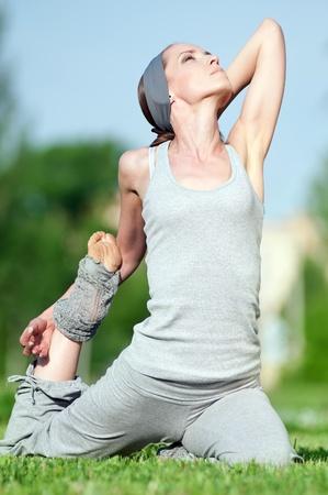haciendo ejercicio: Hermosa mujer haciendo ejercicio estiramiento sobre hierba verde en el Parque. Yoga  Foto de archivo