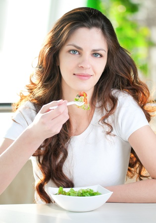 light diet: A young attractive woman sitting in a cafe with a salad