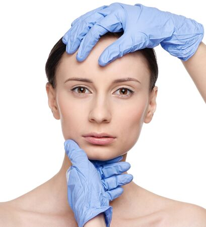 Beautician touch and exam health woman face. Plastic surgery. Isolated Stock Photo - 10283509