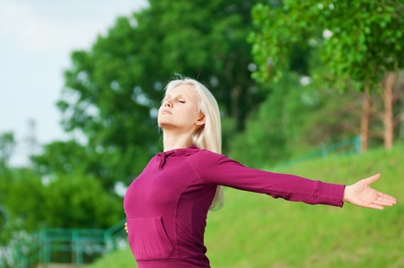 Beautiful young woman doing stretching exercise on green grass at park. Yoga Stock Photo - 10283508