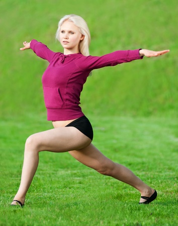 Beautiful young woman doing stretching exercise on green grass at park. Yoga Stock Photo - 10283388
