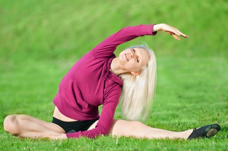 Beautiful young woman doing stretching exercise on green grass at park. Yoga Stock Photo - 10283405