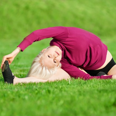 Beautiful young woman doing stretching exercise on green grass at park. Yoga Stock Photo - 10283409