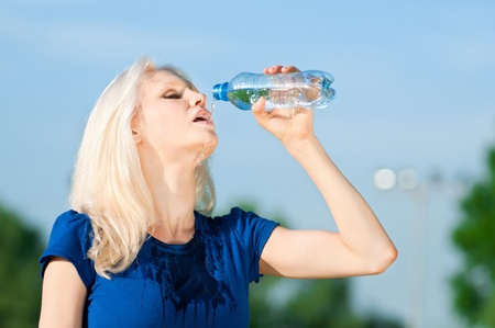Young woman drinking water after fitness exercise Stock Photo - 10283530