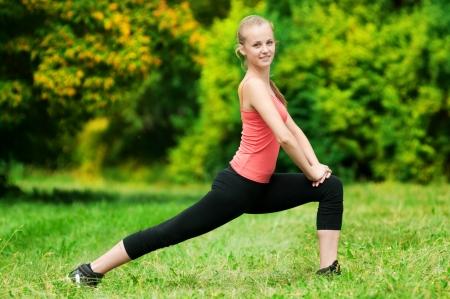 attivit?: Bella giovane donna facendo stretching sulla verde erba al parco. Yoga