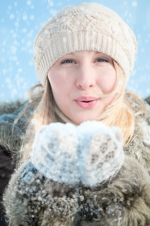 Christmas girl. Winter woman blowing snow photo