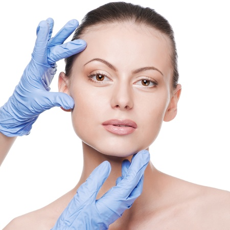 Beautician touch and exam health woman face. Plastic surgery. Isolated Stock Photo - 10322834