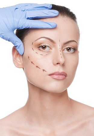 Beautician touch and draw correction lines on woman face. Before plastic surgery operetion. Isolated photo