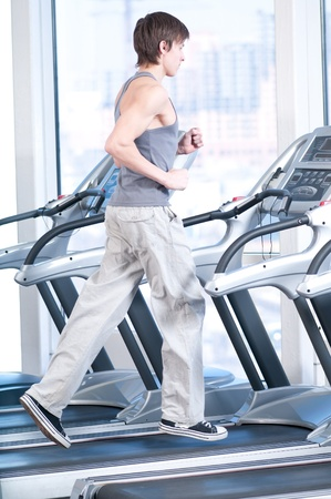 Young man at the gym exercising. Run on on a machine. photo