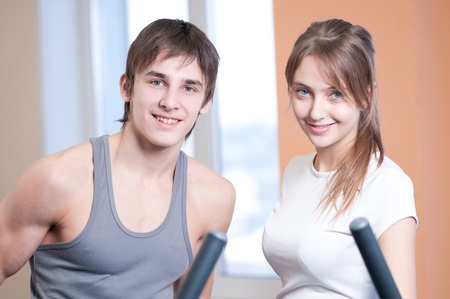 Woman and man train on machine in a gym assisted by personal instructor photo