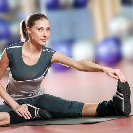 Beautiful sport woman doing stretching fitness exercise at sport gym. Yoga Stock Photo - 10322917