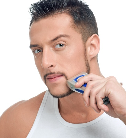 shave: Close up portrait of young handsome man with perfect skin and hair. Shaving by electric shaver Stock Photo