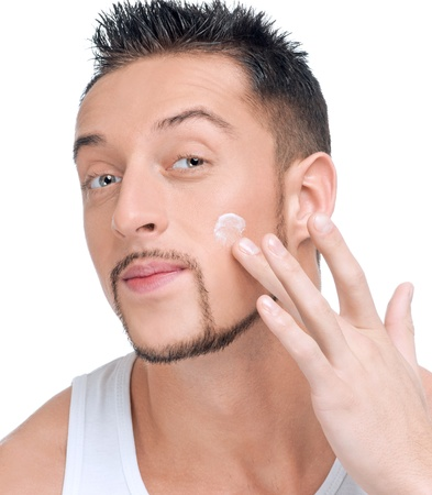Close up portrait of young handsome man applying male cosmetic creme on face photo