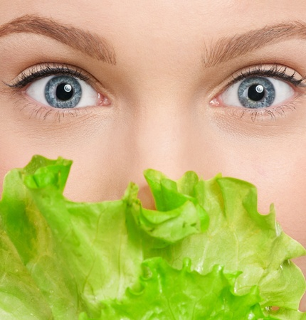 Young beauty woman with green lettuce isolated on white