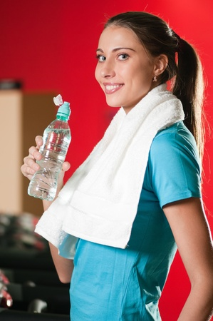 Portrait of a woman at the gym drinking water photo